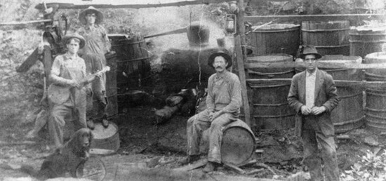 "Hosea Thomas' still workers in Endicott, (Franklin County) Virginia, 1915.  The Martin, Rake, and Thomas families trace their origins to Ireland where local residents learned to make liquor (known in Ireland as ""potchin"") to supplement farm income.  Photo courtesy of the Blue Ridge Institute of Ferrum College."