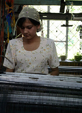 Mary E. Frederickson, Tending an early twentieth century Draper loom made in Massachusetts for use in mills across the Carolinas, Georgia, and Alabama, Margilan, Uzbekistan, 2006.