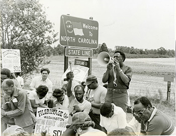 Elaine Tomlin, Joseph Lowery leading a prayer during the 1982 Pilgrimage to Washington for Voting Rights, Peace, Economic Justice, North Carolina, 1982. Courtesy of SCLC records, MARBL, Emory University.