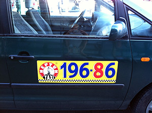 """Lauren Bock, 196-86, Gdansk Airport, Poland, 2012. The song on page 196 in The Sacred Harp is titled """"Alabama""""; the song on page 86, """"Poland."""" This fortuitous image, spotted on the side of a taxi at the Gdansk airport signified for disembarking singers both the physical distance some of them had traveled to attend Camp Fasola Europe and the Poland Sacred Harp Convention and the metaphorical space Sacred Harp singing itself had traveled to make these events possible."""