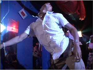 """Video still from Ya Heard Me?, Matt Miller and Stephen Thomas, 2008. In the still, a dancer performs at a """"sissy shakedown"""" at Club Vibe, New Orleans, Louisiana, 2004."""