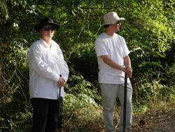 Ellen Schattschneider, Two reenactors playing Klansmen wait near the Moore's Ford Bridge, Walton County, Georgia, July 25, 2009.