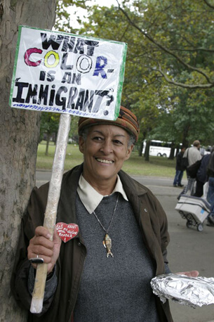 "Stan Schnier, A woman at the Immigrant Workers Freedom Ride holds a sign that asks ""What color is an immigrant?"", Flushing Meadows Corona Park, New York, New York, October 4, 2003."