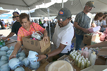 Andrea Booher, Evacuee Umberto Romero gathers food and necessities at the distribution center at the Chalmette Recovery Center set up following Hurricane Katrina, New Orleans, Louisiana, October 22, 2005. South Carolina Cares set up similar centers in Columbia, South Carolina.