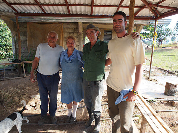 Maria and Augostín (in hat) with their only son Royber and Maria's brother, a neighboring farmer, pictured on the patio at their farm. Pinar del Rio, Cuba, January 2011.
