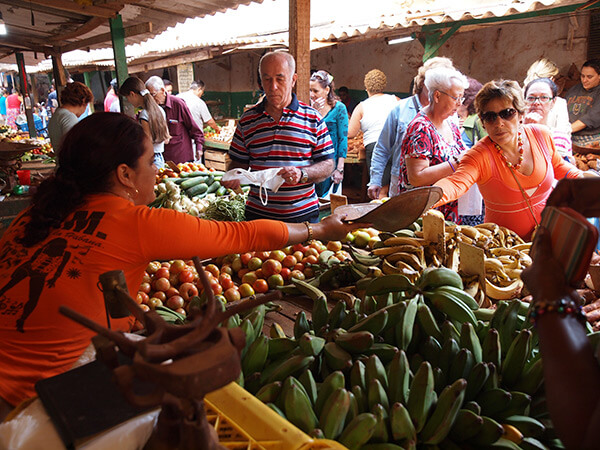 Charles D. Thompson, Jr., Osiris Cueto weighs produce for her customer at the Mercado Agropecuario Beleu. Old Havana, Cuba, December 2010.