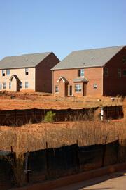 John Howard, Unsold houses amid red clay, Henry County, Georgia, November 2008.