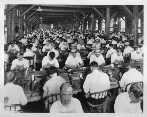 Burgert Brothers, Lector on raised platform reading to cigar workers at Corral Wodiska factory, Tampa, Florida, 1929. Catalog No.: PA 5390.