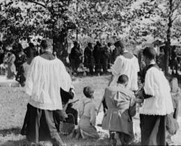 Russell Lee, Library of Congress, Prints & Photographs Division FSA-OWI Collection Reproduction Number: LC-USF33-011901-M2 DLC, Catholic priests blessing members of their congregation, New Roads, Louisiana, 1938.