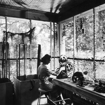 Arnold Eagle, Louisiana Story editor Helen van Dongen operating a Moviola on the porch of the house rented by the Flaherty company, Abbeville, LA, c. 1947. Courtesy of Standard Oil of New Jersey Collection, Special Collections, University of Louisville.