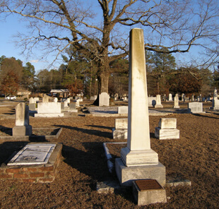 Ellen Schattschneider, Bishop Andrew memorial obelisk in the Andrew family plot (foreground) and the Kitty Tablet at the base of the Gateway Oak (background), Oxford, Georgia, 2005.
