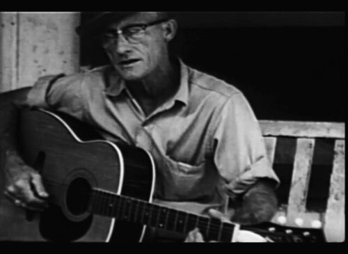 Roscoe Halcomb playing guitar on his front porch in The High Lonesome Sound