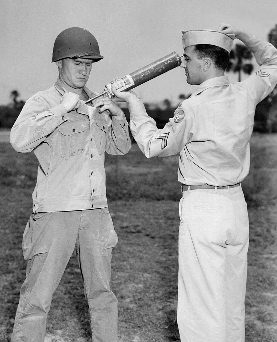 A US soldier is demonstrating DDT-hand spraying equipment while applying the insecticide, ca. 1940s. Courtesy of the CDC Public Health Image Library. Image is in public domain.