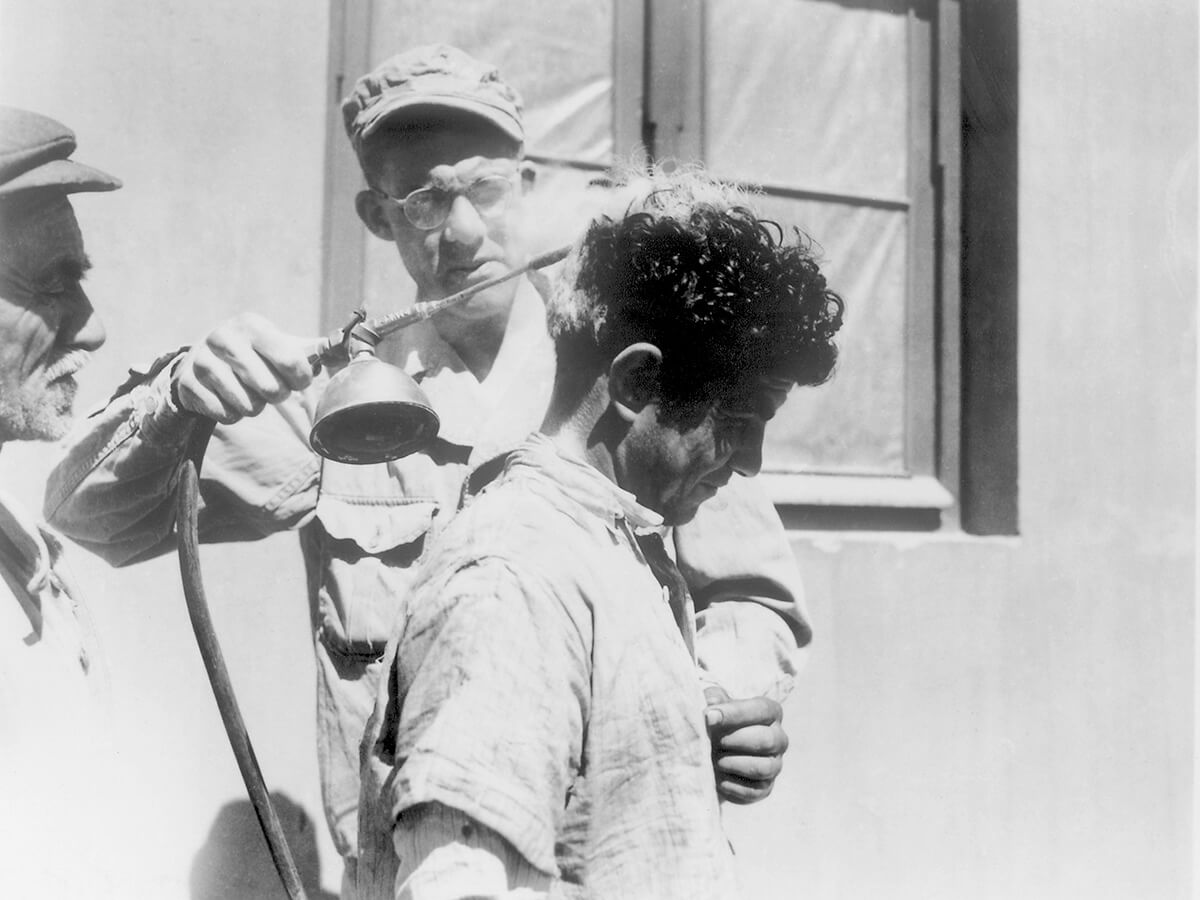 A US Soldier demonstrates the use of DDT-hand spraying equipment. ca. 1940s. Courtesy of the CDC Public Health Image Library. Image is in public domain.