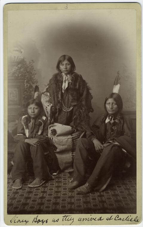 Sioux boys as they arrived at Carlisle, Pennsylvania, ca. 1892. Photograph by unknown creator. Courtesy of New York Public Library Art and Picture Collection Division, digitalcollections.nypl.org/items/510d47e1-1b90-a3d9-e040-e00a18064a99.