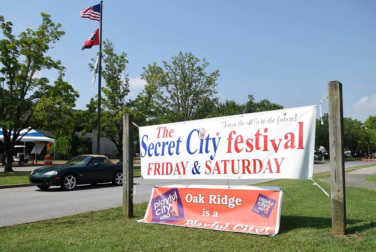 A car drives past a banner advertising the Secret City Festival, Oak Ridge, Tennessee, June 11, 2015. Photograph by Adam Lau. Courtesy of Knoxville News Sentinel.