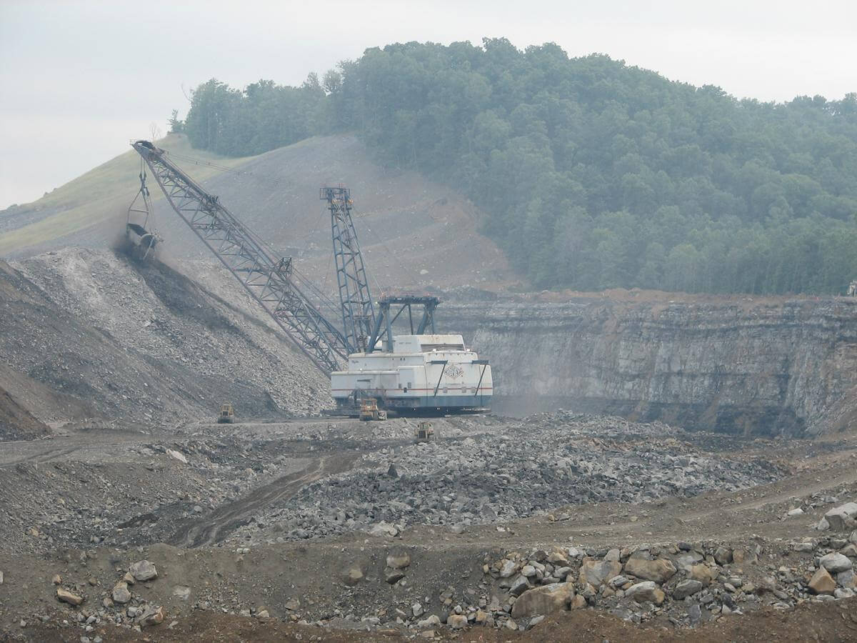 A photograph of a dragline carrying coal surrounded by rocks and dirt.