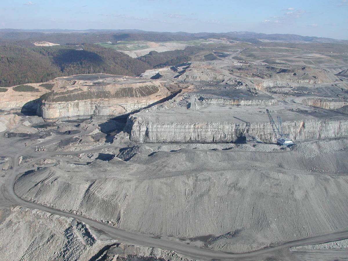 An aerial photograph of a mountaintop removal mine, showing vast expanses of bare, rocky, excavated earth.