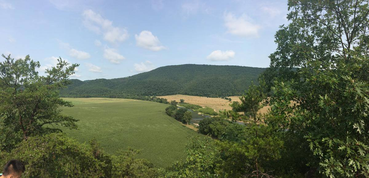 A photograph depicting a landscape of rolling hills and trees in Romney, West Virginia.
