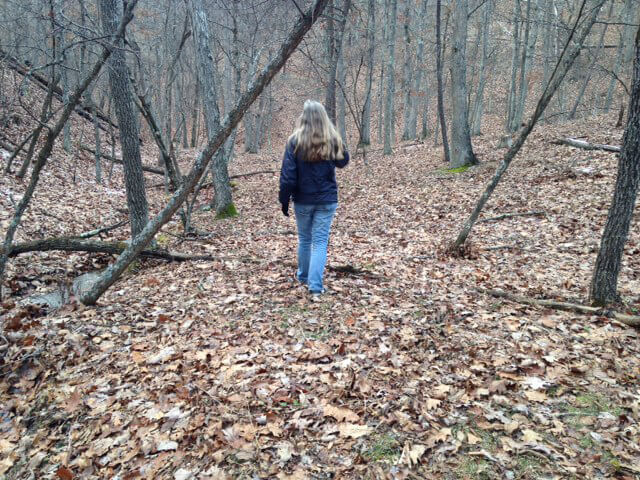 Photograph of Ann Pancake in the woods in winter, walking away from the camera.