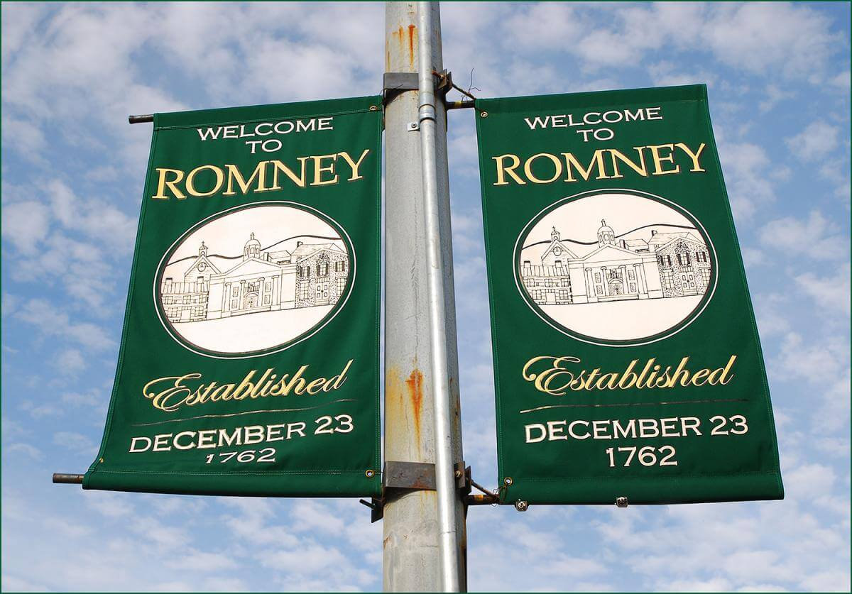 "Cloth sign reading ""Welcome to Romney, Established December 23, 1762"" with blue sky in background."
