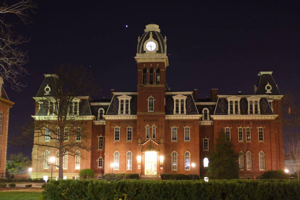 Photograph of a large, well-lit brick university building with a clock tower at night.