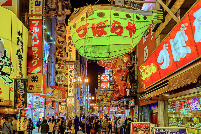 Photograph of a busy street in Osaka, Japan, filled with people, colorful paper lanterns, and glowing signs.