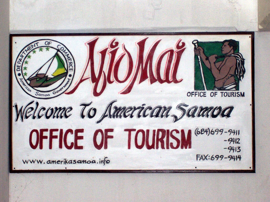 A photograph of a hand painted sign for the American Samoa office of tourism.