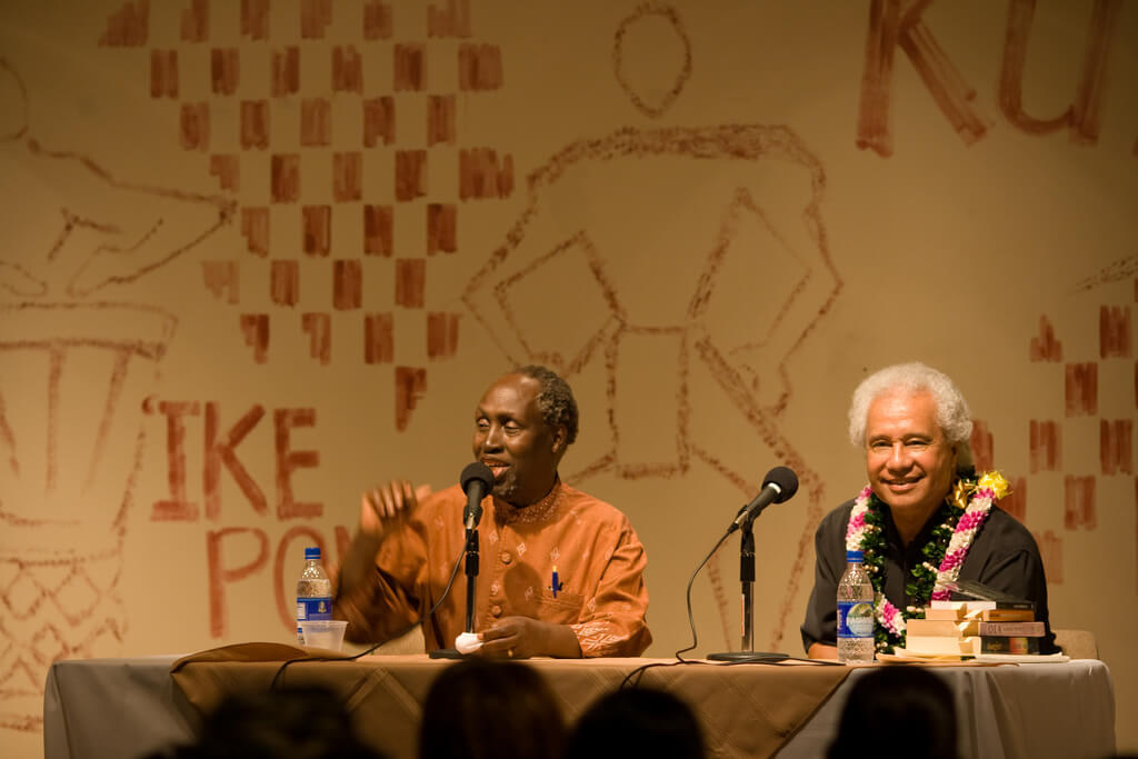 Photograph of Samoan author Albert Wendt and Kenyan writer Ngũgĩ wa Thiong'o, sitting at a table. Ngũgĩ wa Thiong'o is speaking into a microphone and Wendt is smiling.
