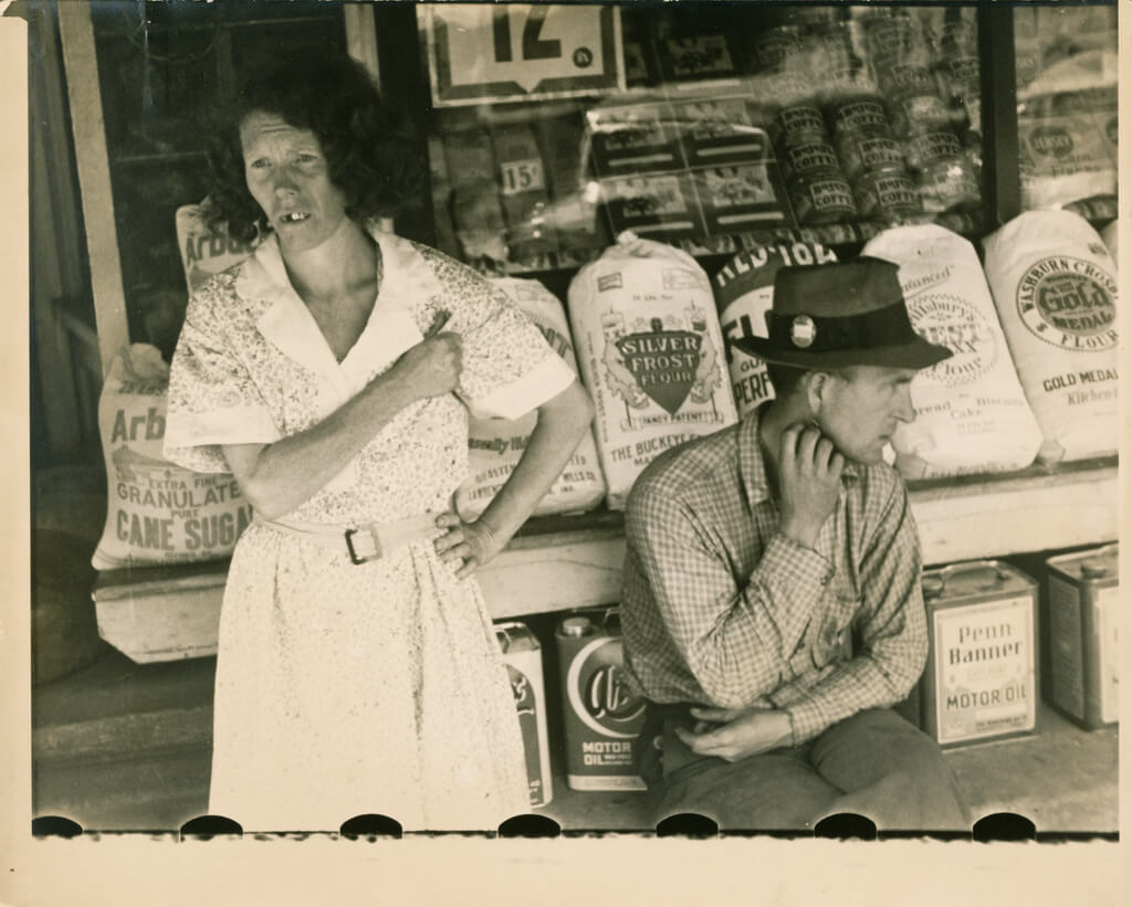Sepia-toned photograph depicting a middle-aged man and woman sitting in front of a grocery store, looking away from the camera.