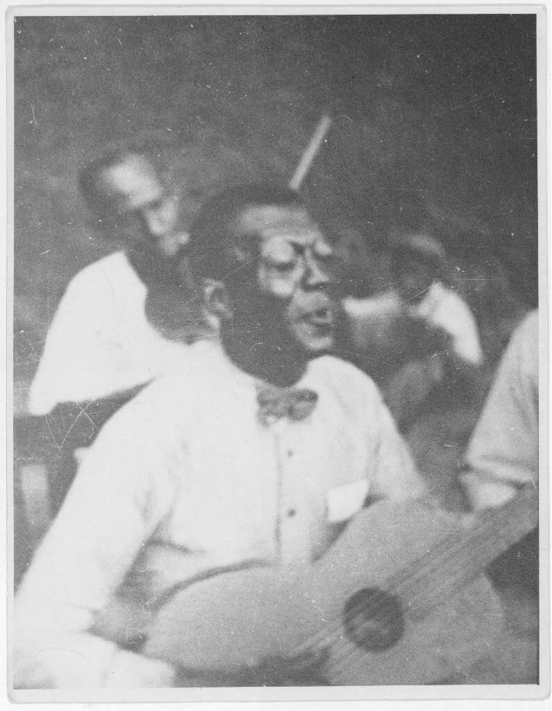"Wilson ""Stavin' Chain"" Jones playing guitar and singing the ballad ""Batson,"" Lafayette, Louisiana, 1934. Photograph by Alan Lomax. The Lomax Collection, Library of Congress. Courtesy of The Library of Congress, Prints and Photographs Division, LC-DIG-ppmsc-00342."