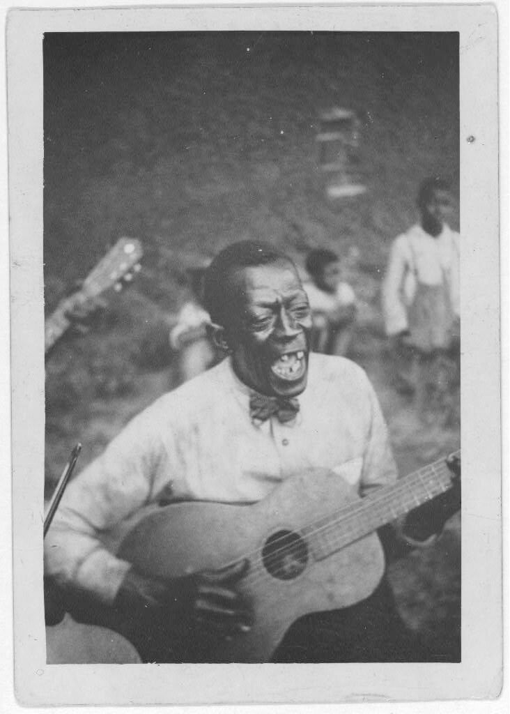 "Wilson ""Stavin' Chain"" Jones playing guitar and singing the ballad ""Batson,"" Lafayette, Louisiana, 1934. Photograph by Alan Lomax. The Lomax Collection, Library of Congress. Courtesy of The Library of Congress, Prints and Photographs Division, LC-DIG-ppmsc-00341."