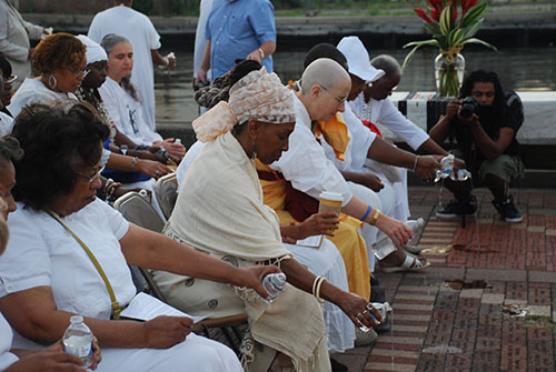 Fells Point, Broadway Pier, Baltimore, Maryland, 2012 (The first ceremony sponsored by MPCPMP). Participants pouring libation to honor African ancestors who experienced the Middle Passage. Photograph by Zora Cobb. Courtesy of MPCPMP.