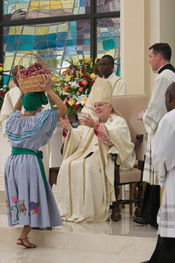 Archbishop Thomas Wenski receiving offertory gifts of fruits and native plants from parishioners, Notre Dame d'Haiti Catholic Church dedication service, Miami, Florida, February 1, 2015. Photo by Ana Rodriguez-Soto. Courtesy of the Archdiocese of Miami.
