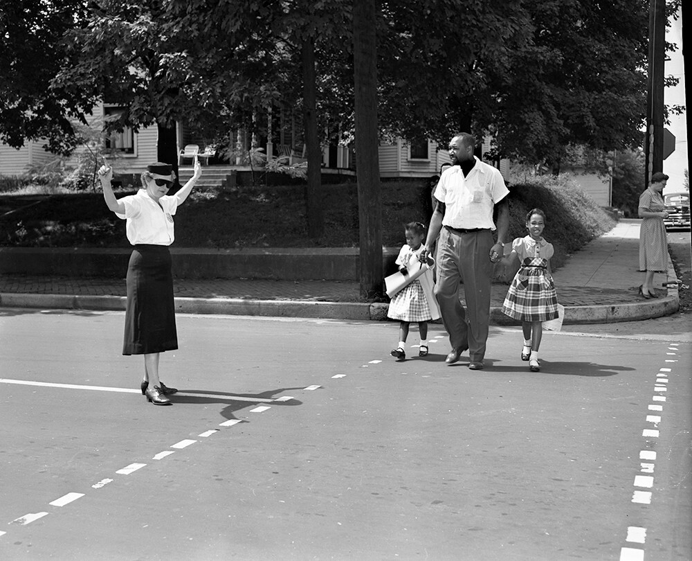 Harold Street walks his daughter Lajuanda (right) and Jacqueline Griffith (left) to Glenn Elementary School, Nashville, TN, September 1957. © Nashville Public Library.​​