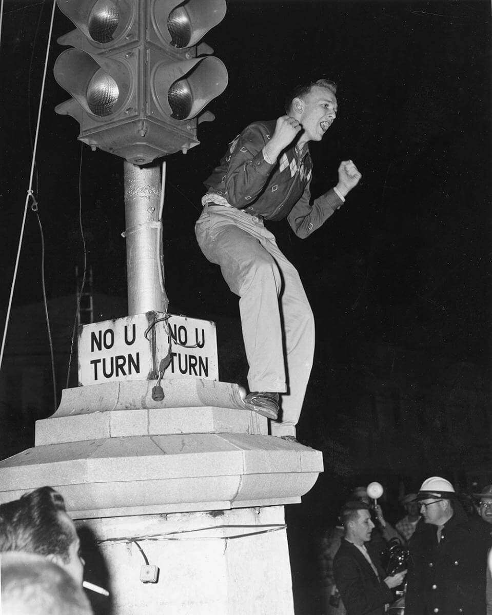 A demonstrator shouts from a traffic light post, Nashville, TN, September 1957. © Nashville Public Library.​​
