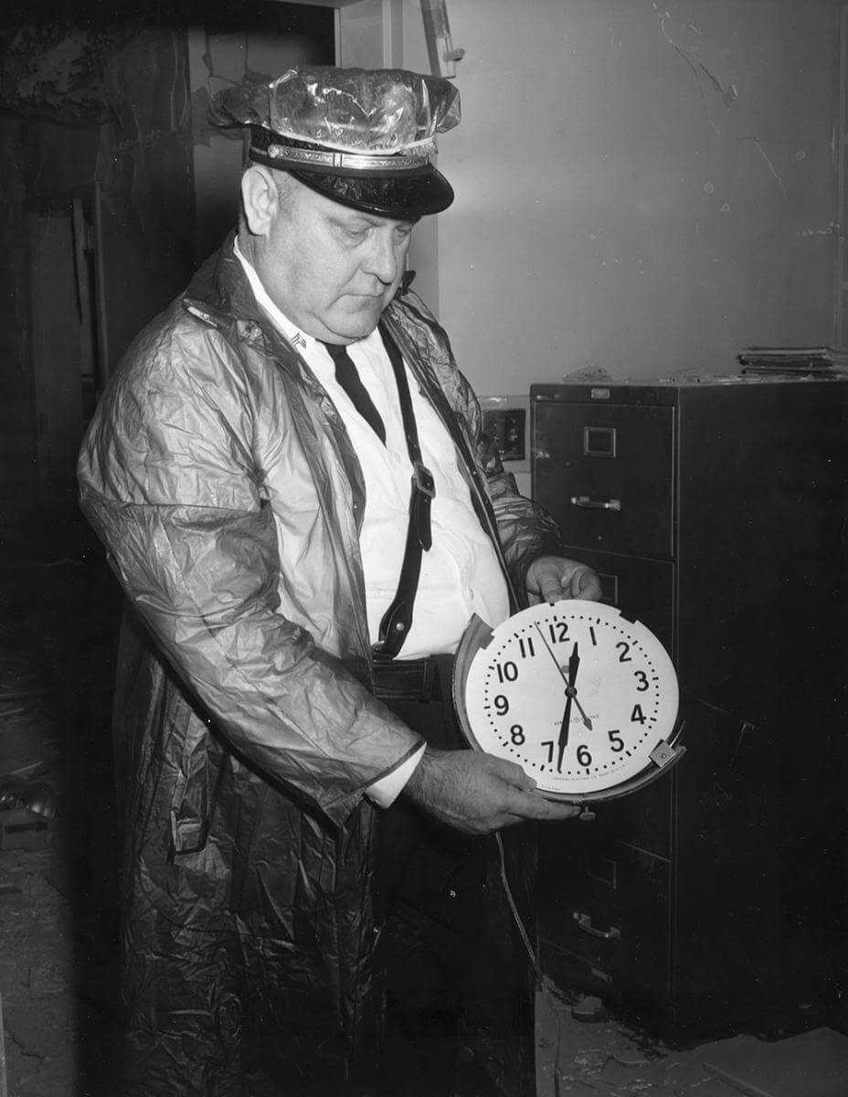 An officer displays a clock stopped at the time of the bomb blast, Nashville, TN, September 1957. © Nashville Public Library.​​