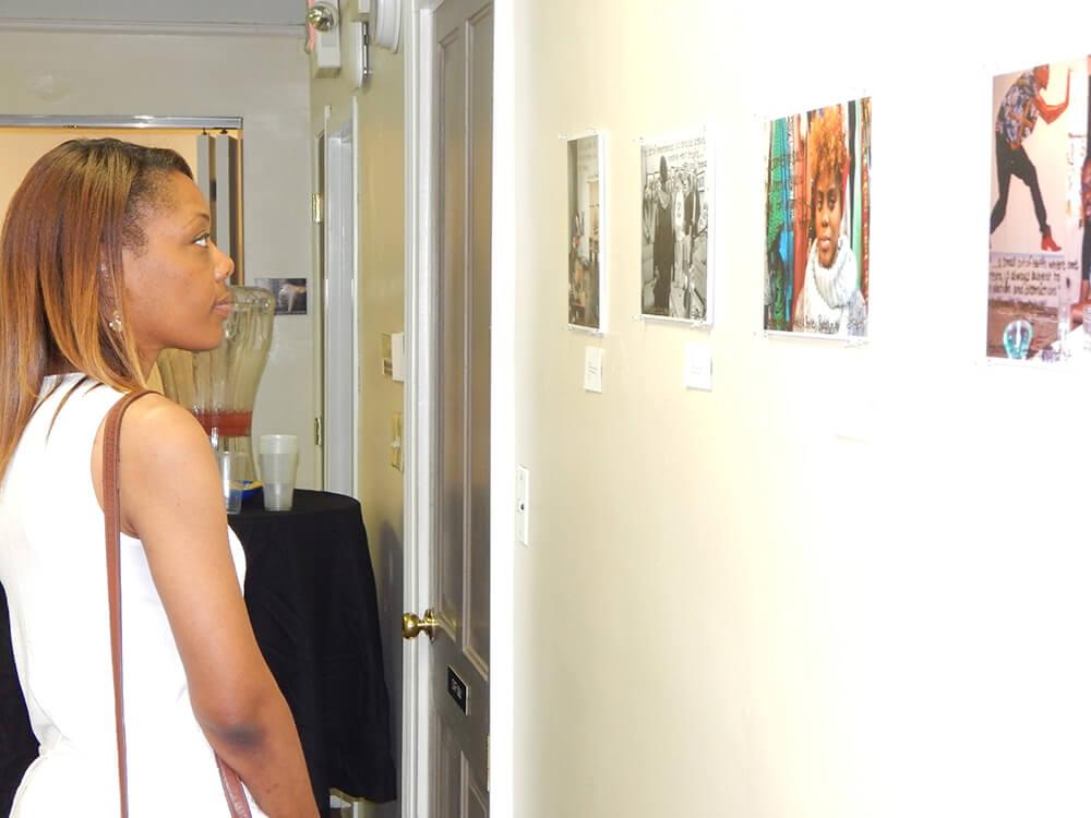 A guest looks at the artwork, Atlanta, Georgia, July 12, 2015. Photograph by Clint Fluker. Courtesy of LiFT Art Salon.