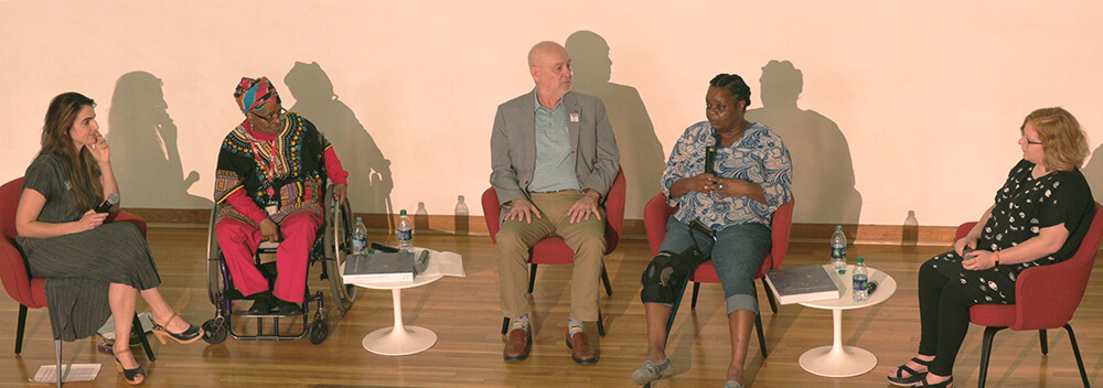 A photograph of four women and one man sitting on a stage in front of a white backdrop. One of the women speaks into a microphone; the others are turned towards her, listening.