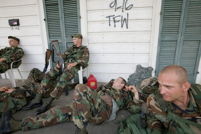 "FEMA News Photo, New Orleans, Louisiana, September 20, 2005. Photograph by Andrea Booher. ""Exhausted National Guardsmen take a break from patrolling isolated communities around New Orleans. Only residents and emergency workers are allowed access following Hurricane Katrina"" (FEMA caption)."