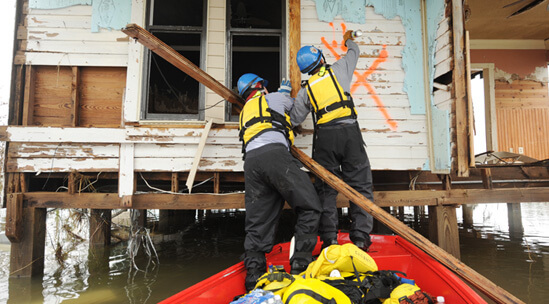 "FEMA News Photo, Sabine Pass, Texas, September 14, 2008. Photograph by Jocelyn Augustino. ""FEMA Urban Search and Rescue Indiana Task Force 1 marks a house as they conduct a search in a neighborhood impacted by Hurricane Ike"" (FEMA caption)."