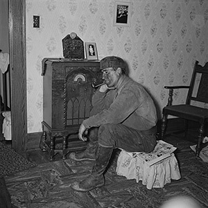 "A coal miner listens to his radio, Westover, West Virginia, 1938. Photograph by Marion Post Wolcott. From the Library of Congress Prints and Photographs Division, LC-USF34-050293-E. From ""The Tennessee Jamboree: Local Radio, the Barn Dance, and Cultural Life in Appalachian East Tennessee,"" by Bradley Hanson."