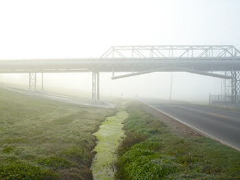 Pipeline and River Road, Donaldsonville, Louisiana, 2010. Photograph by Richard Misrach. Courtesy of Pace/MacGill Gallery, New York; Fraenkel Gallery, San Francisco; and Marc Selwyn Gallery, Los Angeles. © Richard Misrach.