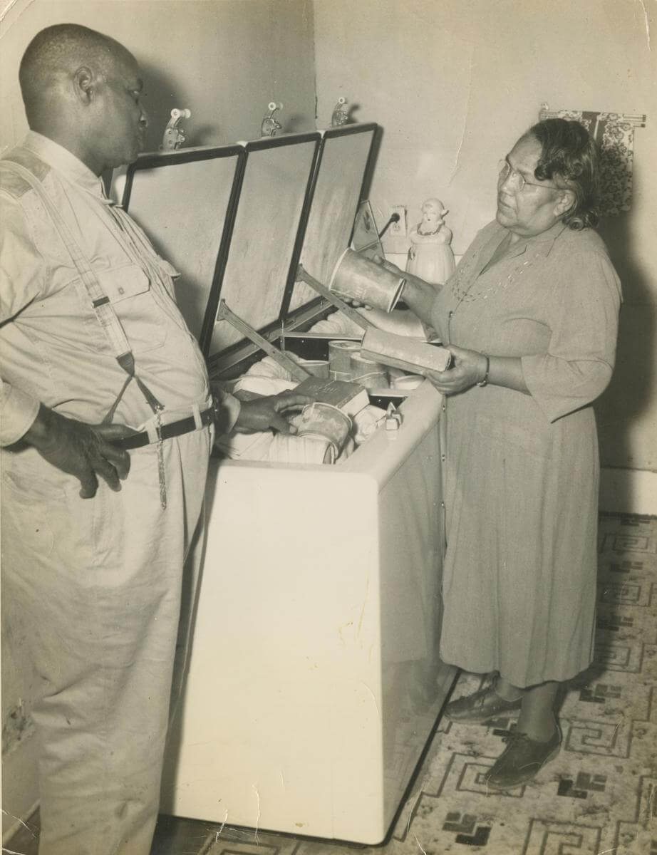 A sepia-toned photograph showing Edward Scott Sr. and Juanita Scott standing at a freezer
