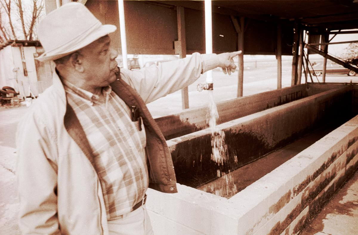 A sepia-toned photograph of Ed Scott at his catfish processing plant, pointing to something outside the frame
