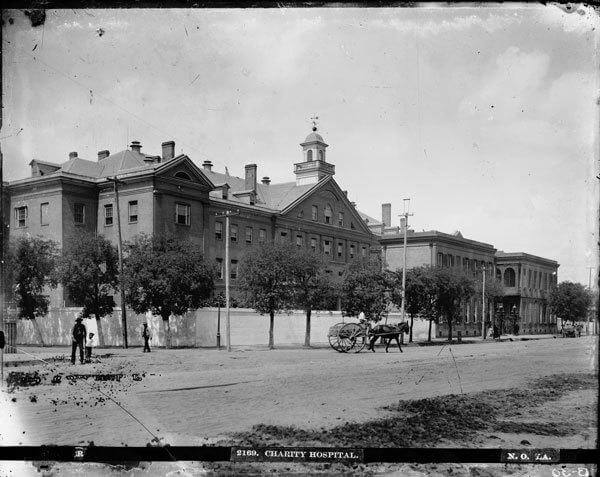 "A black and white photograph of charity hospital, with a horse drawn carriage and three pedestrians in front. Original text at the bottom of the image reads, ""2169. Charity Hospiral. No. 7A."""