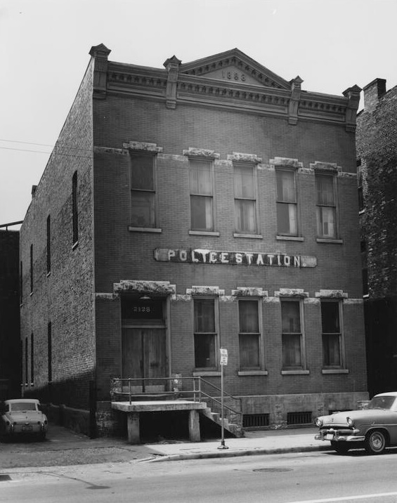 "Black and white photograph of a two-story brick building with a large sign reading ""Police Station."""