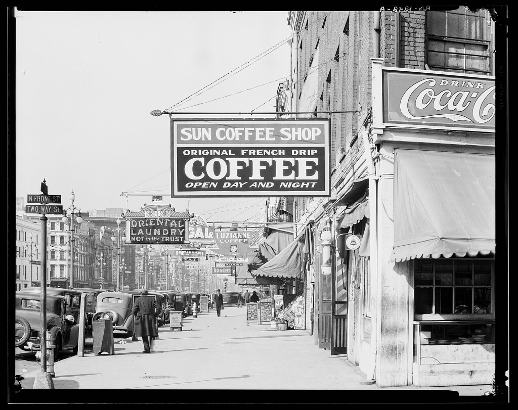 "Black and white image of a New Orleans downtown street, showing a coffee shop with a sign reading, ""Sun Coffee Shop, Original Drench Drip Coffee, Open Day and Night"""