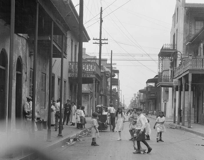 Black and white photograph of children walking and playing in a street.