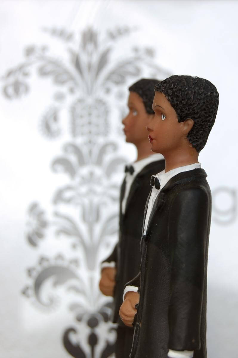 Photograph of two male cake topper figurines side by side.
